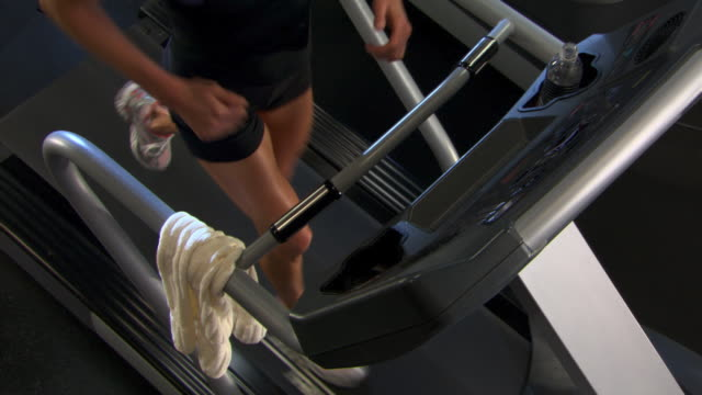 vídeos de stock, filmes e b-roll de overhead of woman running on treadmill - self discipline