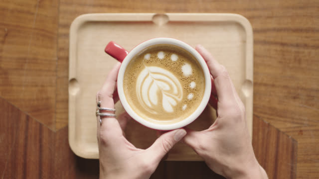 overhead plating shot as hands pick up latte with flower art from wooden tray in coffee shop. - latte stock videos and b-roll footage
