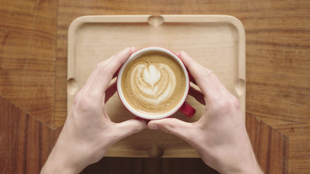 overhead plating shot as hands place latte with flower art on wooden tray in coffee shop. - coffee cup stock videos & royalty-free footage