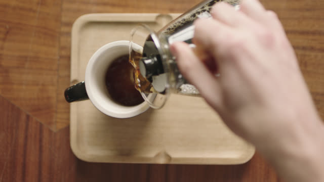 overhead plating shot as hands place mug on tray and pour coffee from pot in coffee shop. - tazza da caffè video stock e b–roll