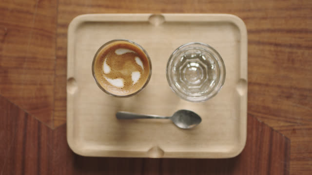 Overhead plating shot of espresso shot with water glass and spoon on wooden tray in hip coffee shop.