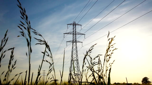 overhead power lines in a rural field - electricity pylon stock videos & royalty-free footage