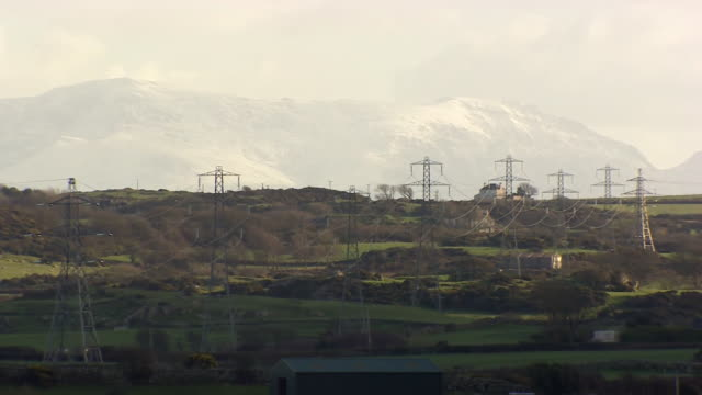 overhead power lines traverse fields on mountainous anglesey wales - field stock videos & royalty-free footage