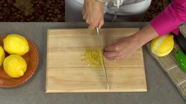 Overhead preparing fresh diced lemon peel as recipe seasoning or garnish.
