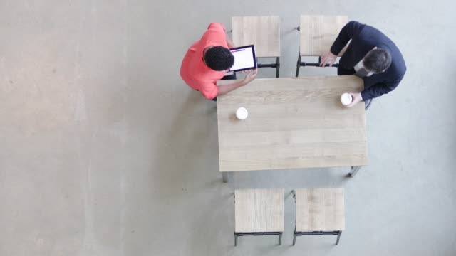 Overhead shot of a colleagues using a digital tablet in a business meeting