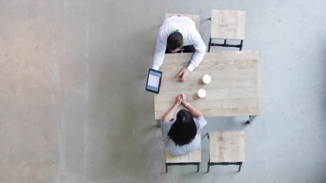 overhead shot of a colleagues using a digital tablet in a business meeting - face to face stock videos & royalty-free footage