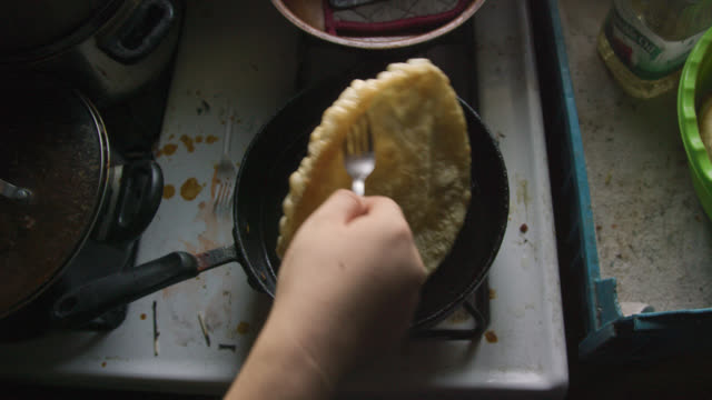 overhead shot of a native american woman's hand using a fork to remove a tortilla (fry bread) from a pan with oil on a stovetop - fried stock videos & royalty-free footage