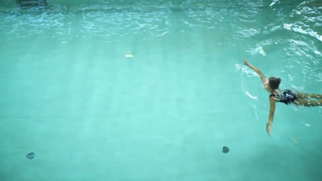 stockvideo's en b-roll-footage met overhead shot van een vrouw zwemmen in een zwembad - binnenbad