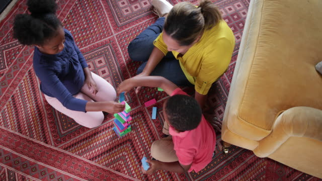 Overhead shot of children playing stacking blocks