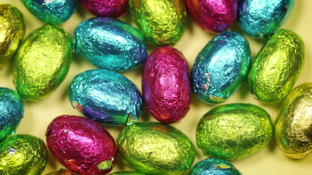 overhead shot of chocolate eggs wrapped in colourful shiny foil - happy easter stock-videos und b-roll-filmmaterial