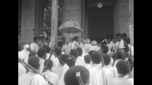 vídeos y material grabado en eventos de stock de overhead shot of crowd of men in white robes many armed with rifles / two shots of selassie walking through crowd under umbrella held by other man /... - servicio religioso