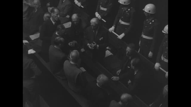 overhead shot of defendants in prisoner's dock talking to one another us mps standing behind them / closer shot of franz von papen talking to hans... - processi di norimberga video stock e b–roll