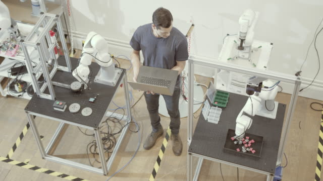overhead shot of engineer programming robotic arms - electrical equipment video stock e b–roll