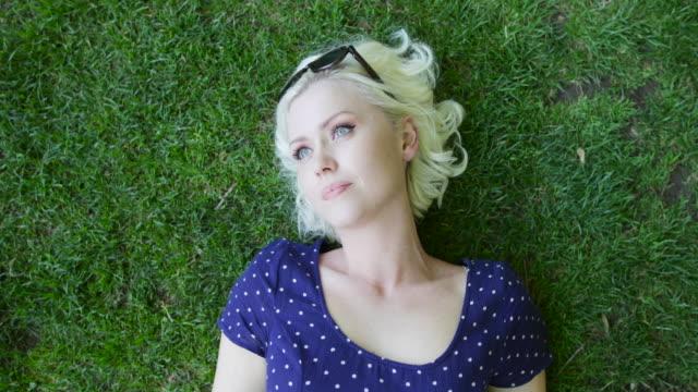 overhead shot of female sunbathing in park - lying down stock videos & royalty-free footage