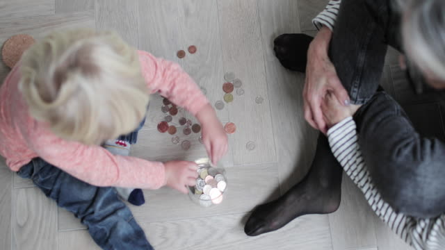 vídeos de stock e filmes b-roll de overhead shot of grandmother helping grandchild count pocket money - atividade bancária