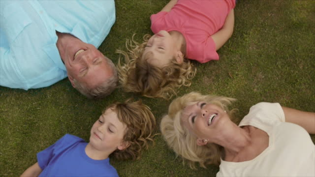 stockvideo's en b-roll-footage met overhead shot of grandparents and grandchildren lying on grass in garden. - zus