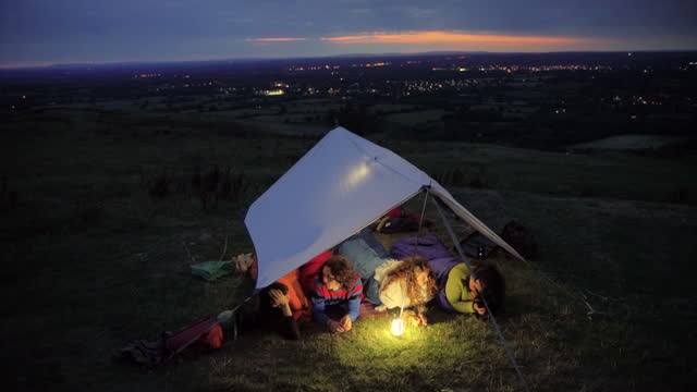 overhead shot of group of friends chatting in their tent at night - east sussex stock videos & royalty-free footage