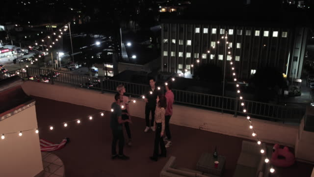 overhead shot of group of friends dancing at a rooftop party - patio video stock e b–roll