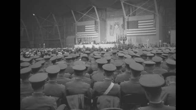 Overhead shot of guests sitting in Gillis Field House for ceremony / ground level shot from behind cadets as they sit and watch ceremony / shot of...