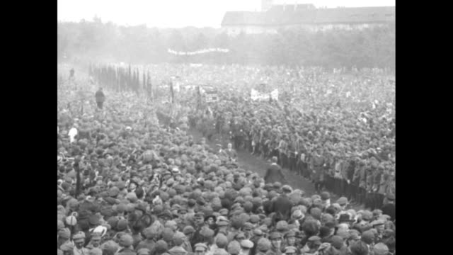 overhead shot of huge crowd / two shots of communists, many holding flags, marching through crowd / communists holding flags in middle of crowd /... - communism stock videos & royalty-free footage