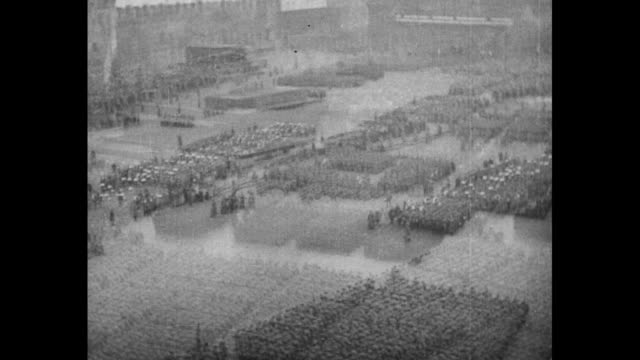 Overhead shot of huge number of soldiers standing in formations in Red Square / overhead shot of soldiers marching in formations past Lenin's...