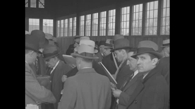 vidéos et rushes de overhead shot of large crowd of men at the racetrack, all wearing hats / men betting, getting odds / horses on the track running - hasard