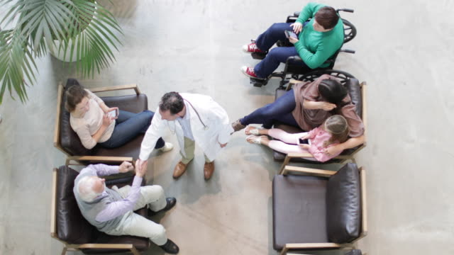 stockvideo's en b-roll-footage met overhead shot of medical doctor greeting senior male in waiting room - wide shot