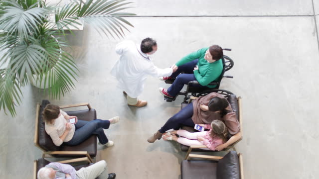 overhead shot of medical doctor greeting woman in wheelchair in waiting room - part of a series stock-videos und b-roll-filmmaterial