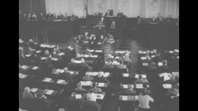 Overhead shot of members of parliament sitting and listening to Konrad Adenauer speaking from rostrum / closer view of Adenauer speaking about...
