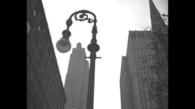 vídeos de stock e filmes b-roll de overhead shot of newly completed rockefeller center / two shots from ground level of buildings in center / three shots of emblems on buildings / view... - estátua de atlas
