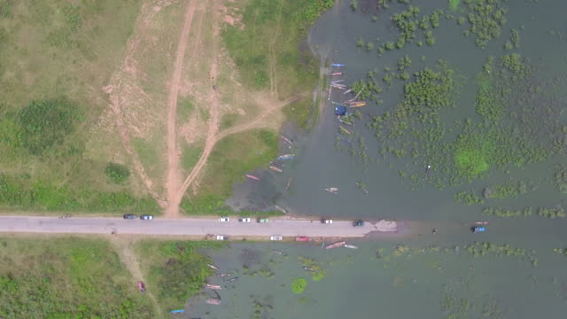 overhead shot of rural street cover by water, road running through submerged fields - danneggiato video stock e b–roll