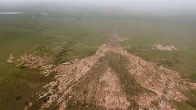 overhead shot of sandstone peak and the green pasture made with the drone through clouds (chimney rock, nebraska, usa) - sandstone stock videos & royalty-free footage