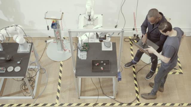 overhead shot of team programming a robotic arm - fließband stock-videos und b-roll-filmmaterial