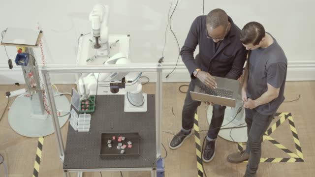 vídeos y material grabado en eventos de stock de overhead shot of team programming a robotic arm - brazo robótico herramientas de fabricación