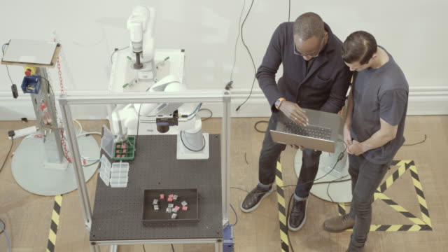 vidéos et rushes de overhead shot of team programming a robotic arm - corvée domestique