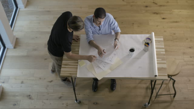 Overhead shot of two young businessmen working on project, developing business project.