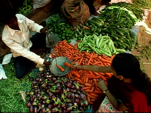 overhead shot of vendor weighing carrots for woman at outdoor market / bangalore, karnataka, india - scales stock videos & royalty-free footage