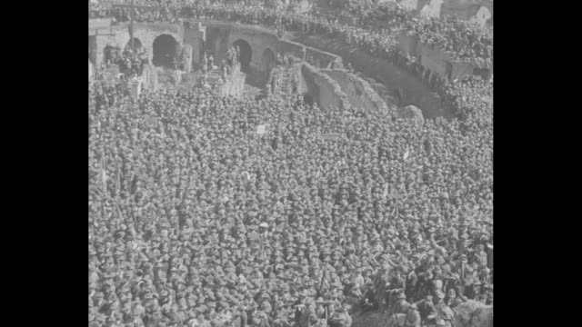 overhead shot of veterans of world war i lined up along walkway on upper level of colosseum / pan across crowd of veterans on ground level and upper... - benito mussolini stock videos & royalty-free footage