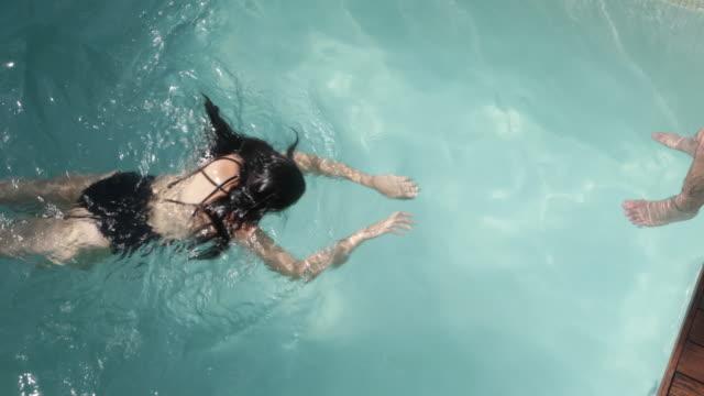 Overhead shot of woman swimming across pool.