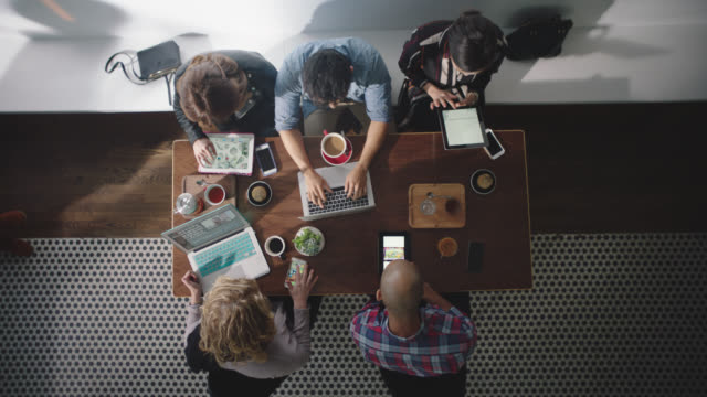 WS. Overhead shot of young people immersed in technology with smartphones, tablets, and laptops at coffee shop table.