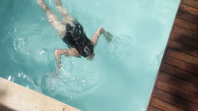 overhead shot woman swimming across pool. - one piece swimsuit stock videos and b-roll footage