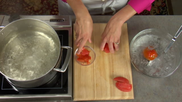 overhead slicing a tomato prior to adding as ingredient in a baking recipe. - bowl stock videos & royalty-free footage