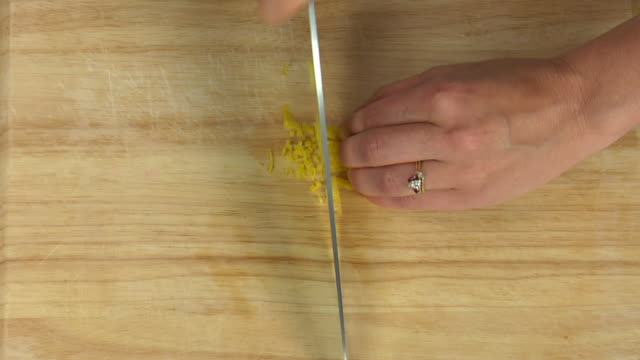 overhead slicing and dicing fresh lemon peel for use in a recipe. - peel plant part stock videos and b-roll footage