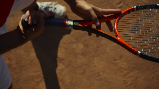 overhead slow motion close up of man twirling tennis racket on clay court - tennis racket stock videos & royalty-free footage