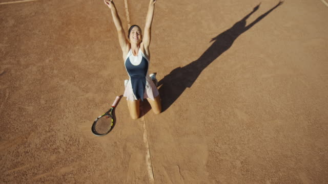 vídeos de stock e filmes b-roll de overhead slow motion of clay tennis court as woman comes in to frame with sweeping forehand and drops to knees in celebration - ténis calçado desportivo