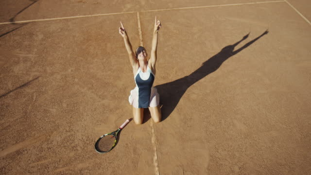overhead slow motion of clay tennis court with woman making sweeping forehand and dropping to knees in celebration - racket stock videos and b-roll footage