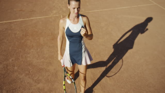 Overhead slow motion of woman on clay tennis court making fist in celebration and walking off