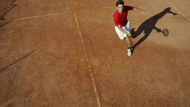 overhead slow motion shot of man on clay tennis court celebrating victory - tennis video stock e b–roll