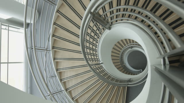 overhead timelapse of business colleagues walking down spiral staircase discussing work - spiral staircase stock videos & royalty-free footage