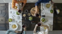 Overhead top view table four caucasian friends eating carbonara italian spaghetti pasta at lunch or dinner,drinking,toasting together  with red wine glasses.Summer party at home in modern house vide